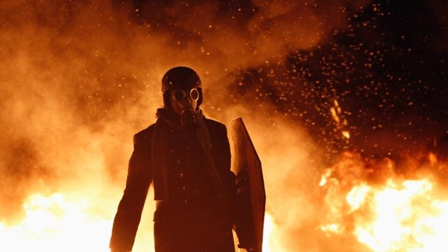 Jan. 23, 2014: A pro-European protester wears a gas mask during street violence in Kiev.