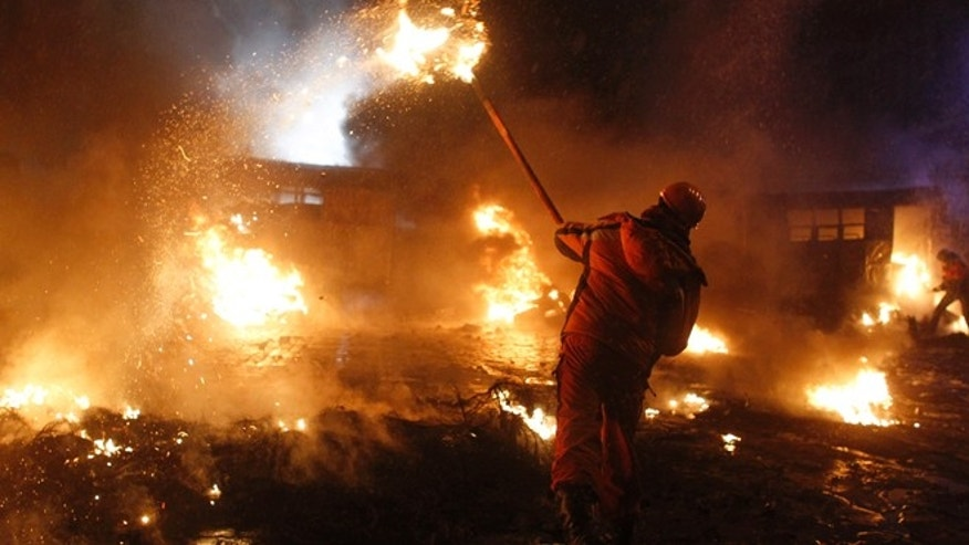 Jan. 22, 2014: A pro-European protester throws a burning tyre during clashes with riot police in Kiev.