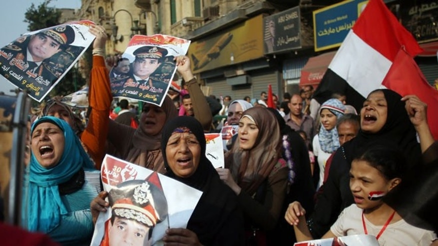 In this file photo taken Sunday, Oct. 6, 2013, Egyptians chant pro-army slogans and hold posters of Egyptian Defense Minister Gen. Abdel-Fattah el-Sissi as they celebrate the 6th of October, 1973 war anniversary, in Tahrir Square, Cairo, Egypt.