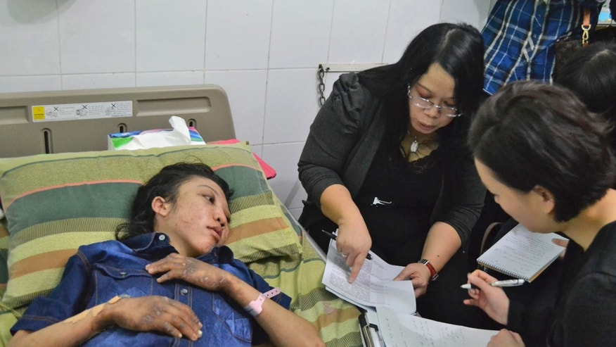In this photo released by Indonesian National Police, Erwiana Sulistyaningsih, left, an Indonesian maid who was allegedly tortured by her employer in Hong Kong, is interviewed by Hong Kong police investigators at a hospital where she is treated in Sragen, Central Java, Indonesia, Tuesday, Jan. 21, 2014. Hong Kong police officers arrived at the hospital Tuesday to interview Sulistyaningsih as Indonesia's President Susilo Bambang Yudhoyono expressed his concern and anger over the alleged brutality. (AP Photo/Indonesian National Police)