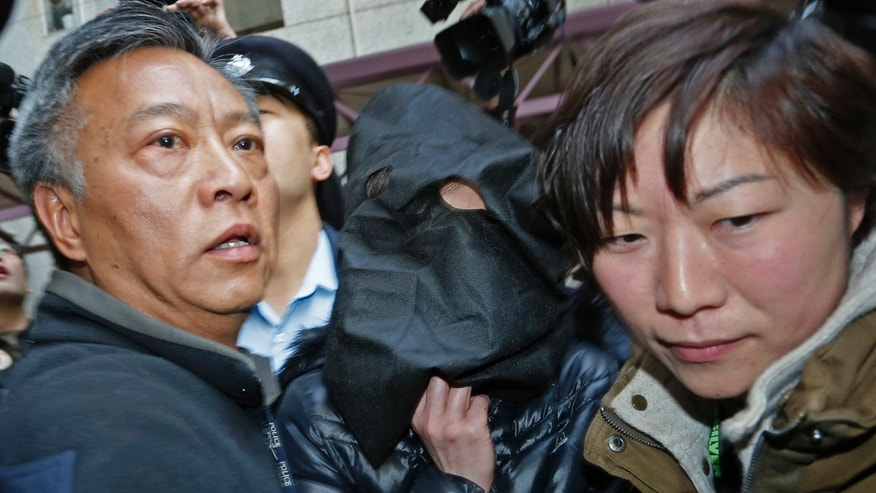 A 44-year-old woman surnamed Law, covered her head with a black hood, center, is escorted by police officers for an investigation at her home in Hong Kong, Tuesday, Jan. 21, 2014. The woman was arrested on Monday accused of beating her Indonesian maid in a case that has triggered outrage over its alleged brutality. (AP Photo/Vincent Yu)