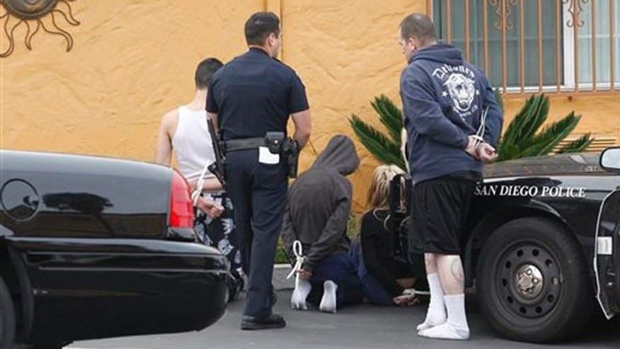 Local law enforcement and FBI agents detain several people after a raid on El Cajon Boulevard, Wednesday, Jan. 8, 2014 in San Diego.  Seventeen people were arrested Wednesday in California, Arizona and New Jersey under an indictment that accuses a San Diego-based street gang of running a vast prostitution ring. The gang based in San Diego's increasingly gentrified North Park neighborhood operated a prostitution ring spanning 46 cities in 23 states, recruiting women and girls by promising luxurious lifestyles, prosecutors said. Gang members allegedly branded the women with tattoos and bar codes and traded them among themselves.  (AP Photo/U-T San Diego, John Gibbins)  NO SALES; COMMERCIAL INTERNET OUT