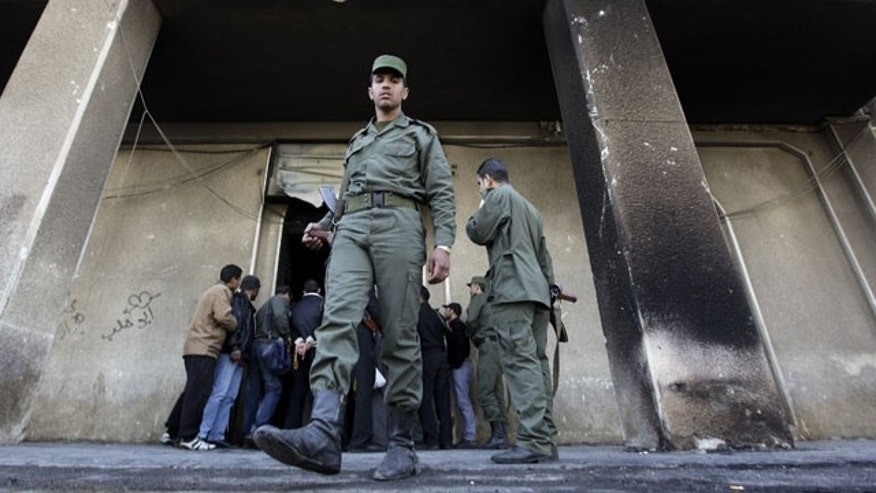 FILE - In this Monday, March 21, 2011 file photo, A Syrian army soldier steps out from the burned court building that was set on fire by Syrian anti-government protesters, in the southern city of Daraa, Syria. (AP)
