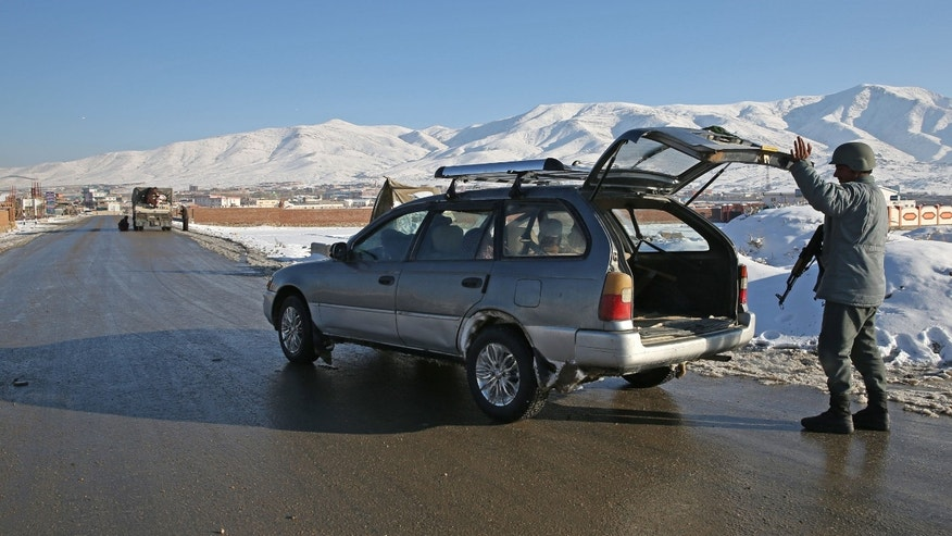 "In this Thursday, Jan. 9, 2014 photo, Hekmatullah, an Afghan policeman searches the trunk of a car at a check post in Kabul-Bamiyan road, on the outskirts of Maidan Shahr, capital of Wardak province Afghanistan. Locals call it ""Death Road."" The 30 kilometer (18 mile) stretch of road heading west from here has seen so many beheadings, kidnappings and other Taliban attacks in recent years that it's become a virtual no man's land, cutting off the Hazara minority from their homeland in Afghanistan's rugged mountainous center. (AP Photo/Massoud Hossaini)"