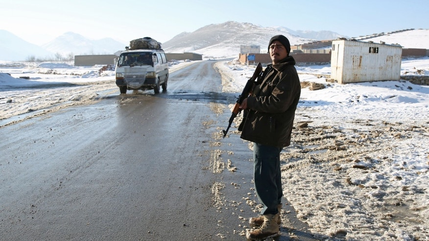 "In this Thursday, Jan. 9, 2014 photo, Habibullah, an Afghan policeman stands guard at a check post in Kabul-Bamiyan road, on the outskirts of Maidan Shahr, capital of Wardak province Afghanistan. Locals call it ""Death Road."" The 30 kilometer (18 mile) stretch of road heading west from here has seen so many beheadings, kidnappings and other Taliban attacks in recent years that it's become a virtual no man's land, cutting off the Hazara minority from their homeland in Afghanistan's rugged mountainous center. (AP Photo/Massoud Hossaini)"