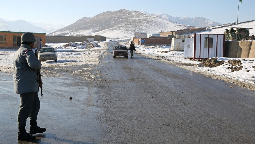 "In this Thursday, Jan. 9, 2014 photo, an Afghan policemen stand guard at a check post in Kabul-Bamiyan road, on the outskirts of Maidan Shahr, capital of Wardak province Afghanistan, Thursday, Jan. 9, 2014. Locals call it ""Death Road."" The 30 kilometer (18 mile) stretch of road heading west from here has seen so many beheadings, kidnappings and other Taliban attacks in recent years that it's become a virtual no man's land, cutting off the Hazara minority from their homeland in Afghanistan's rugged mountainous center. (AP Photo/Massoud Hossaini)"