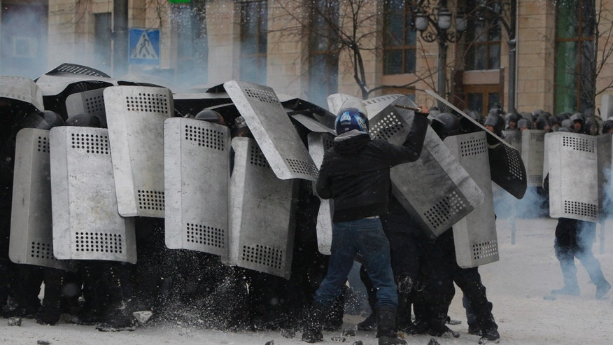 A protester attacks police in central Kiev, Ukraine, Wednesday, Jan. 22, 2014. Police in Ukraineís capital on Wednesday tore down protester barricades and chased demonstrators away from the site of violent clashes, hours after two protesters died after being shot, the first violent deaths in protests that are likely to drastically escalate the political crisis that has gripped Ukraine since late November. (AP Photo/Sergei Grits)