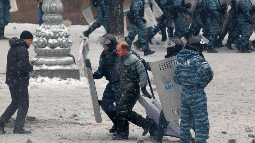 Police officers detain a protester during  clashes in central Kiev, Ukraine, Wednesday, Jan. 22, 2014. Police in Ukraine's capital on Wednesday tore down protester barricades and chased demonstrators away from the site of violent clashes, hours after two protesters died after being shot, the first violent deaths in protests that are likely to drastically escalate the political crisis that has gripped Ukraine since late November. (AP Photo/Sergei Grits)