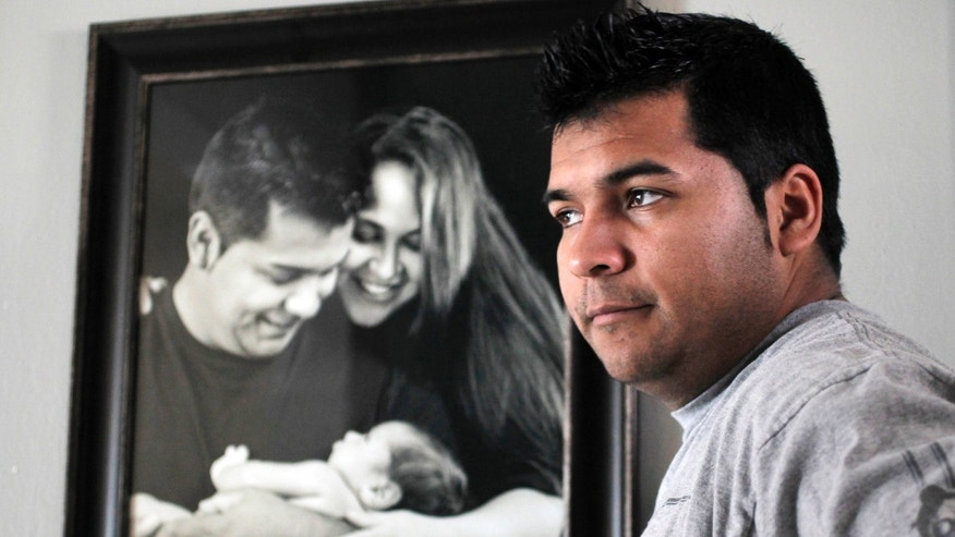 FILE - In this Friday, Jan. 3, 2014 file photo, Erick Munoz stands with an undated copy of a photograph of himself, left, with wife Marlise and their son Mateo, in Haltom City, Texas. Munozâs attorneys said in a statement Wednesday, Jan. 22, 2014, that the fetus that Marlise Munoz is carrying has several âabnormalities,â including a deformation of the lower body parts that make it impossible to determine its gender. (AP Photo/The Fort Worth Star-Telegram, Ron T. Ennis, File)
