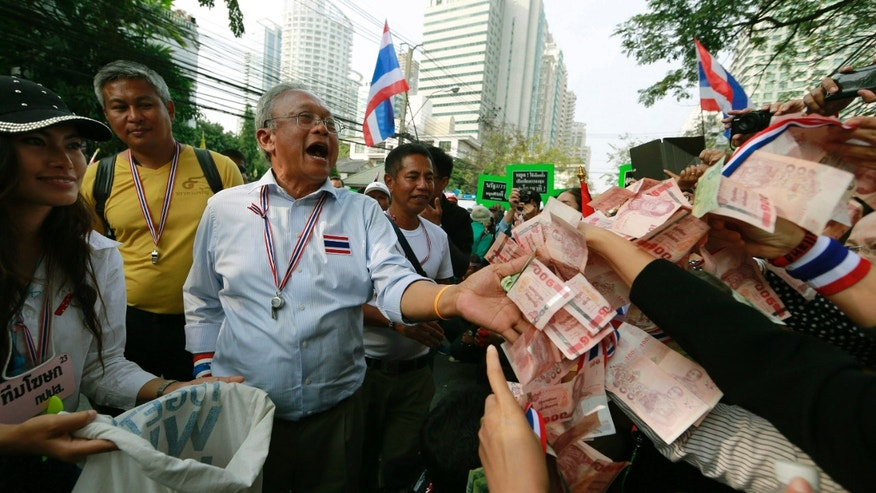 Supporters hand money to Thai anti-government protest leader Suthep Thaugsuban during a march Thursday, Jan. 23, 2014, in Bangkok, Thailand. As a state of emergency came into effect Wednesday in the Thai capital, defiant protesters marched on government offices and defaced the wall outside of national police headquarters, while a prominent government supporter in the country's northeast was the target of a shooting attack. (AP Photo/Wason Wanichakorn)