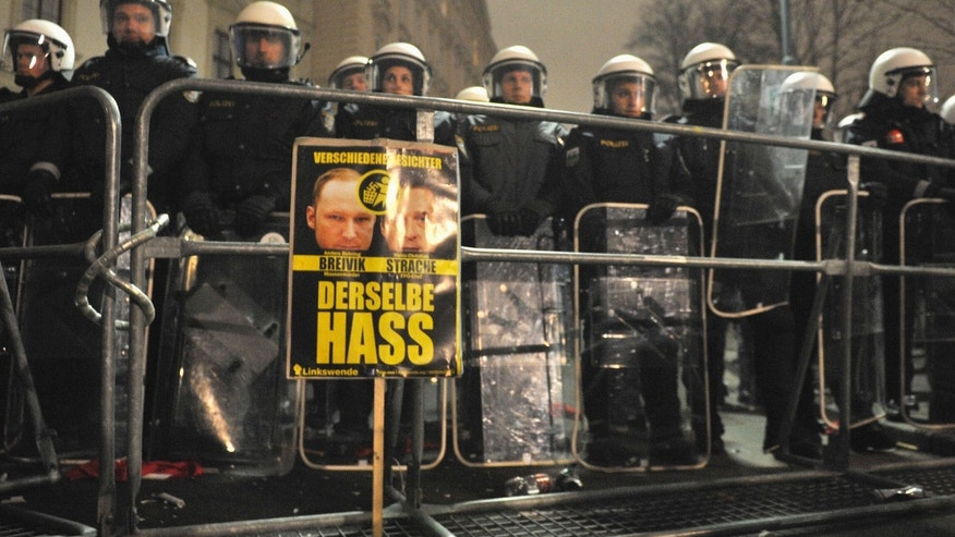 "A banner stands in front of a police line, with the words: ""Different faces, Anders Breivik, Heinz Christian Strache, the same hate"" during a demonstration against a  ball being hosted at the Hofburg palace by the right-wing FPOE party Friday, Jan. 24, 2014, in downtown Vienna, Austria.  (AP Photo/Hans Punz)"