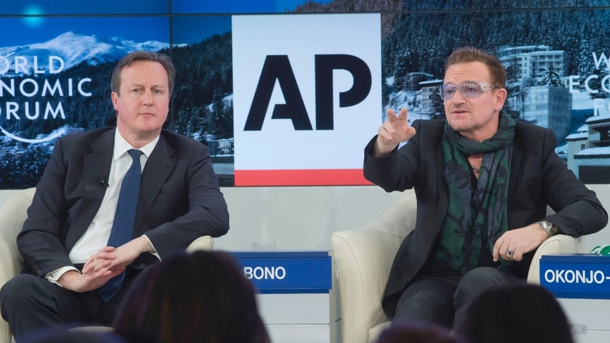 "British Prime Minister David Cameron, left, listens to rock star Bono during the panel discussion  ""The Post-2015 Goals: Inspiring a New Generation to Act"", the fifth annual Associated Press debate, at the World Economic Forum in Davos, Switzerland, Friday, Jan. 24, 2014.  (AP Photo/Michel Euler)"