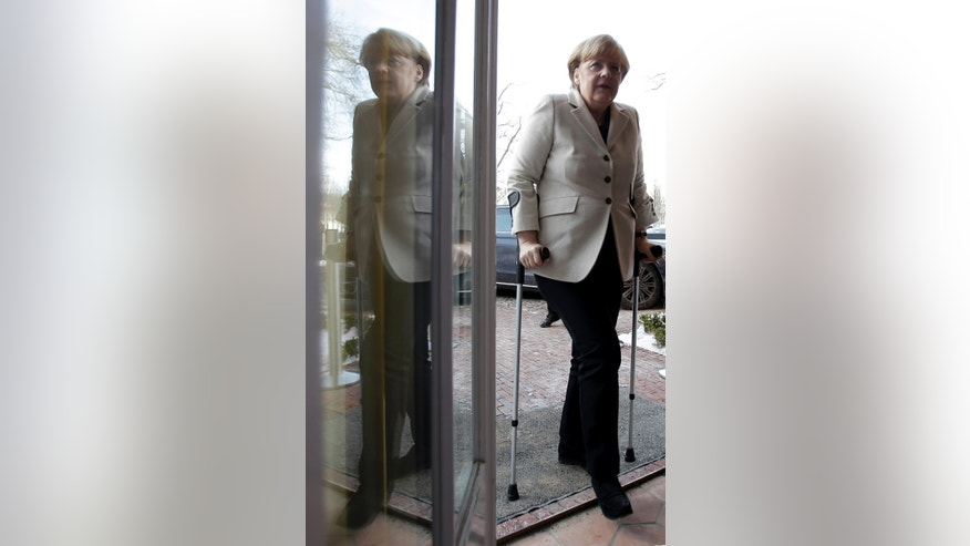 German Chancellor Angela Merkel is reflected in a glass door as she arrives for a press conference after a cabinet meeting as part of a two day closed meeting of the German government at the Meseberg palace near Berlin, Germany, Thursday, Jan. 23, 2014. Merkel uses crutches after a skiing accident. (AP Photo/Michael Sohn)