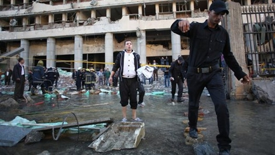 Jan. 24, 2014: Egyptian police officers walk thorough water that came out of the underground water pipe after a blast at the Egyptian police headquarters as firefighters check the damage in downtown Cairo.