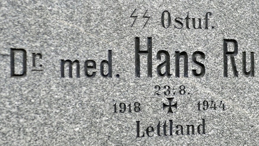 This picture taken Tuesday, Jan. 21, 2014, shows a gravestone where a name marked with the SS runes proudly worn by the elite Nazi troops responsible for most of the crimes of the Holocaust at the main cemetary in Graz, Austria. Austrian law bans such symbols, and those displaying them face criminal charges and potential prison terms. Yet the emblems reflecting this country's darkest chapter in history endure here, and officials here appear either unable or unwilling to do away with them. (AP Photo/Hans Punz)