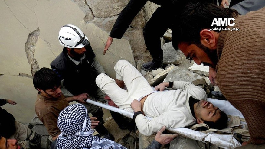 In this picture taken on on Thursday, Jan. 23, 2014, a citizen journalism image provided by Aleppo Media Center (AMC), an anti-Bashar Assad activist group which has been authenticated based on its contents and other AP reporting, Syrian residents and rescue workers carry an injured man from a building damaged, according to AMC, attacked by the Syrian forces airplanes in Aleppo, Syria. AMC said the attack was by the Syrian forces airplanes. Direct talks planned between President Bashar Assad's government and the Western-backed opposition hoping to overthrow him were scrapped Friday, and the two sides will meet a U.N. mediator in different rooms at different times. (AP Photo/Aleppo Media Center, AMC)