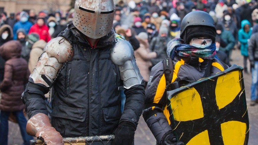 FILE - In this file photo taken on Monday, Jan.  20, 2014, Protesters clad in improvised protective gear prepare for a clash with police in central Kiev, Ukraine. Protesters in Kiev used improvised protective gear to protect themselves from stun grenades, rubber bullets and tear gas during clashes with police in central Kiev this week? After a night of vicious streets battles, anti-government protesters and police clashed anew Monday in the Ukrainian capital Kiev. (AP Photo/Evgeny Feldman, file)