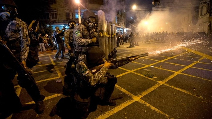 FILE - In this June 30, 2013 file photo, military police fire tear gas at protestors near Maracana stadium as Brazil and Spain play the final Confederations Cup soccer match in Rio de Janeiro, Brazil. Brazil has created a special riot force to help police control demonstrations expected during the 2014 World Cup, and authorities say they will not let protesters get too close to the stadiums. (AP Photo/Silvia Izquierdo, File)