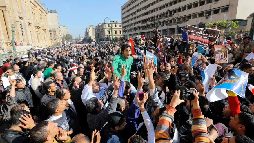 Egyptians shout anti-terrorism slogans as they demonstrate in front the site of a blast at the Egyptian police headquarters, at right, and the Museum of Islamic Art, at left, in downtown Cairo, Egypt, Friday, Jan. 24, 2014. A car bomb struck the main Egyptian police headquarters Friday in the heart of Cairo, killing several people in a hugely symbolic attack on the eve of the third anniversary of the 2011 uprising that toppled longtime autocratic ruler Hosni Mubarak. (AP Photo/Amr Nabil)
