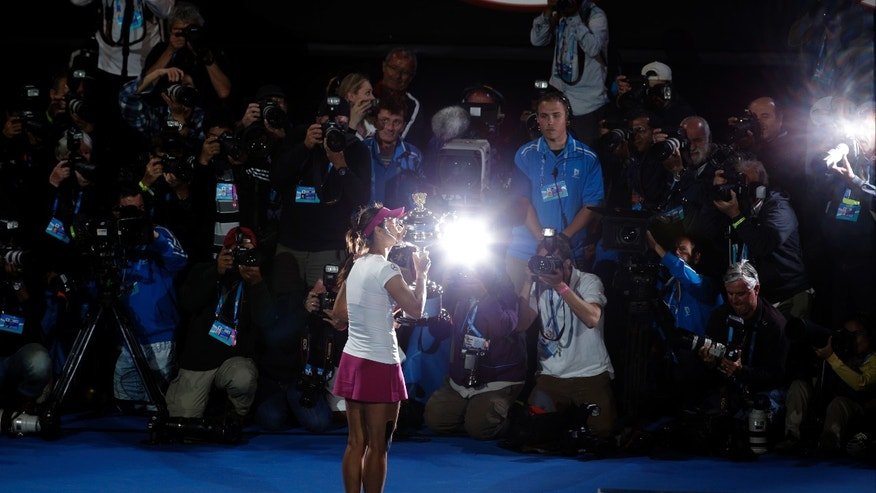 Li Na of China kisses the championship trophy after defeating Dominika Cibulkova of Slovakia in their women's singles final at the Australian Open tennis championship in Melbourne, Australia, Saturday, Jan. 25, 2014. (AP Photo/Aijaz Rahi)