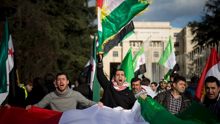 "Jan. 24, 2014 - Syrian opposition demonstrators shout anti Syrian government slogans as they demonstrate with Syrian opposition and Kurdish flags outside the United Nations headquarters in Geneva, Switzerland. Syrian state television says the government delegation at the peace negotiations in Geneva will leave Jan. 25th if  ""serious talks"" do not start."