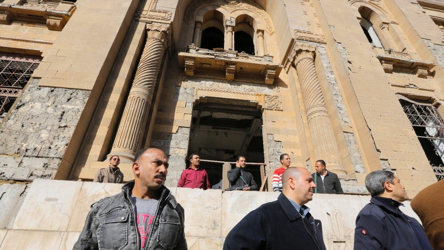 Egyptian plainclothes policemen stand guard in front of the Museum of Islamic Art at the site of a suicide car bomb at the Egyptian police headquarters in downtown Cairo, Egypt, Friday, Jan. 24, 2014. Egypt's antiquities minister, Mohammed Ibrahim, said the explosion badly damaged the facade of the 19th century museum and artifacts inside, including a rare collection of Islamic art objects dating back to 1881. (AP Photo/Amr Nabil)