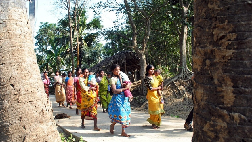 Santhal tribal women carry children and walk in a village where a woman was gang raped, allegedly on the direction of a village council at Subalpur, in Birbhum district, about 180 kilometers (110 miles) north of Kolkata, the capital of the eastern Indian state of West Bengal, Friday, Jan. 24, 2014. The woman told police that Monday's attack came as punishment for falling in love with a man from a different community and religion. The case has brought fresh scrutiny to the role of village councils, common in rural Indian, which decide on social norms in the village. (AP Photo)