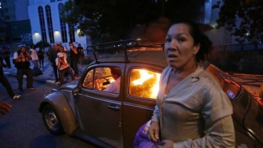 CORRECTS HOW THE CAR CAUGHT FIRE - A man drives his car which caught fire when he tried to drive past a burning barricade set up by protesters who were demanding better public services and protesting against the upcoming World Cup soccer tournament in Sao Paulo, Brazil, Saturday, Jan. 25, 2014. The woman was also in the vehicle but got out when it caught fire. Last year, millions of people took to the streets across Brazil complaining of higher bus fares, poor public services and corruption while the country spends billions on the World Cup, which is scheduled to start in June. (AP Photo/Nelson Antoine)