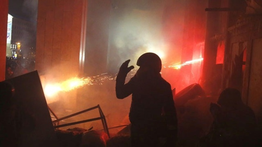 January 26, 2014: Protesters attack the Ukrainian House in central Kiev, Ukraine. Early Sunday, demonstrators were throwing firebombs into the building and setting off fireworks, and police responded with tear gas. (AP Photo/Sergei Grits)