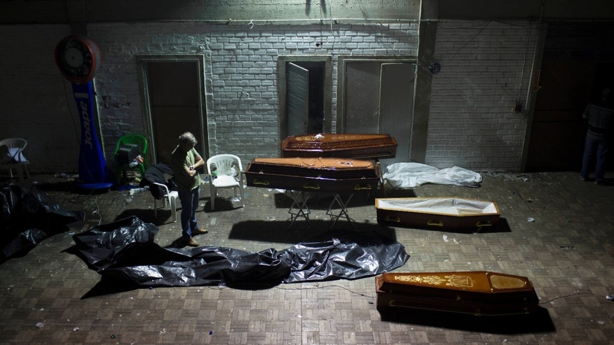 CORRECTS ANNIVERSARY DATE OF FIRE - FILE - In this Jan. 27, 2013 file photo, a man stands near coffins containing the remains of victims from a nightclub fire after the bodies were identified at a gymnasium in Santa Maria city, Rio Grande do Sul state, Brazil. Never again, officials vowed a year ago, would Brazil see a horror like the nightclub fire that killed 242 young men and women, all suffocated by toxic smoke that filled a windowless bunker of a building with no emergency exits. Yet as Brazil marks the anniversary Monday, Jan. 27, 2014, of the deadly blaze at the Kiss nightclub, almost nothing concrete has been done at any level of government to improve fire safety. (AP Photo/Felipe Dana, File)