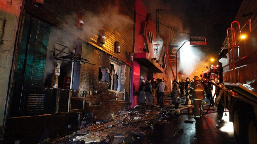 CORRECTS ANNIVERSARY DATE OF FIRE - FILE - In this Jan. 27, 2013 file photo, firefighters work to douse a fire at the Kiss Club in Santa Maria city, Rio Grande do Sul state, Brazil. Never again, officials vowed a year ago, would Brazil see a horror like the nightclub fire that killed 242 young men and women, all suffocated by toxic smoke that filled a windowless bunker of a building with no emergency exits. Yet as Brazil marks the anniversary Monday, Jan. 27, 2014, of the deadly blaze at the Kiss nightclub, almost nothing concrete has been done at any level of government to improve fire safety. (AP Photo/Agencia RBS, File)