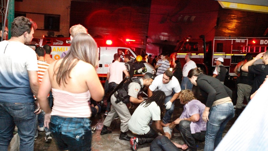 People help an injured man, victim of a nightclub fire, in Santa Maria city, Brazil, on Jan. 27, 2013.