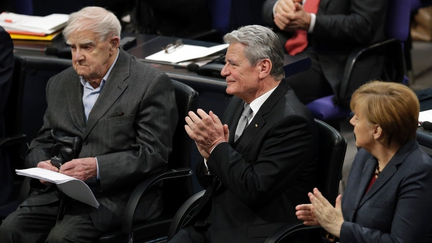 German Chancellor Angela Merkel, right, and German President Joachim Gauck, center, applaud to 95-year-old Russian author Daniil Granin, left, during a ceremony marking the Day of Remembrance for the Victims of National Socialism at the German Parliament, Bundestag, in Berlin, Germany, Monday, Jan. 27, 2014. (AP Photo/Michael Sohn)