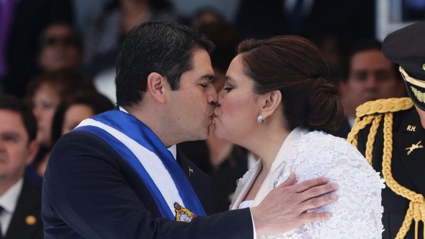 Honduras' President Juan Orlando Hernandez, left, kisses his wife Ana Rosalinda de Hernandez after his swearing in ceremony as new president in Tegucigalpa, Honduras, Monday, Jan. 27, 2014. Hernandez faces many challenges president since Honduras has one of the highest murder rates in the world and well as being one of the poorest countries in the Americas. (AP Photo/Arnulfo Franco)
