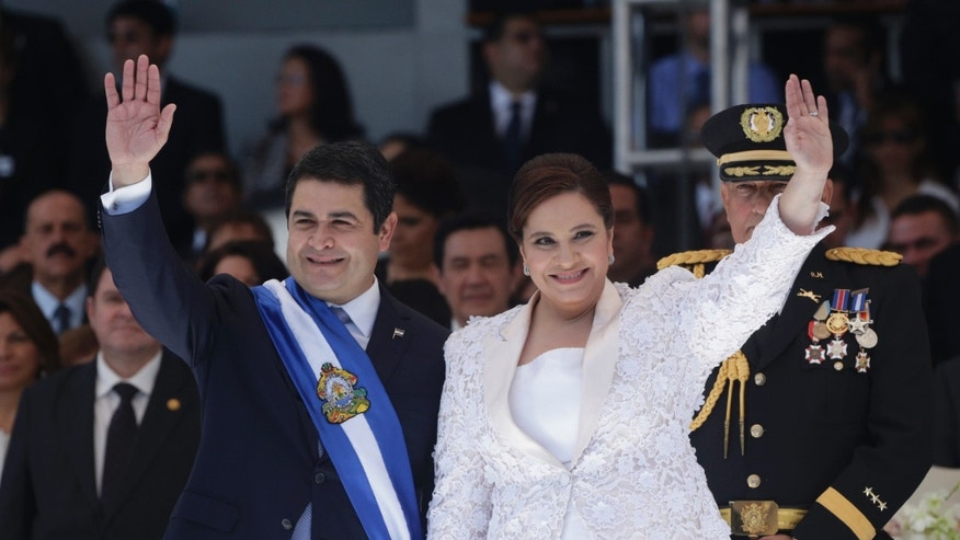 Honduras' President Juan Orlando Hernandez, left, and his wife Ana Rosalinda wave after his swearing in ceremony as new president in Tegucigalpa, Honduras, Monday, Jan. 27, 2014. (AP Photo/Arnulfo Franco)