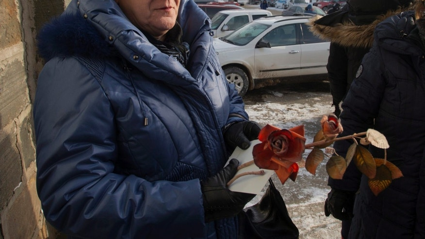 A woman holds a flower as she arrives for a commemorative service, Sunday, Jan. 26, 2014, for victims of last week's fatal fire at a seniors residence in L'Isle-Verte, Quebec. (AP Photo/The Canadian Press, Ryan Remiorz)