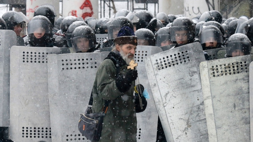 FILE  In this file photo taken on Wednesday, Jan.  22, 2014, an Orthodox priest prays in front of police officers as they block a street after clashes in central Kiev, Ukraine. As a barricade of blazing tires belched thick black smoke, a line of priests stood between angry protesters and ominous riot police. Every freezing morning, priests sing prayers to demonstrators gathered on the Ukrainian capital's main square, a solemn and soothing interlude to vehement speeches calling for revolution.(AP Photo/Efrem Lukatsky, file)
