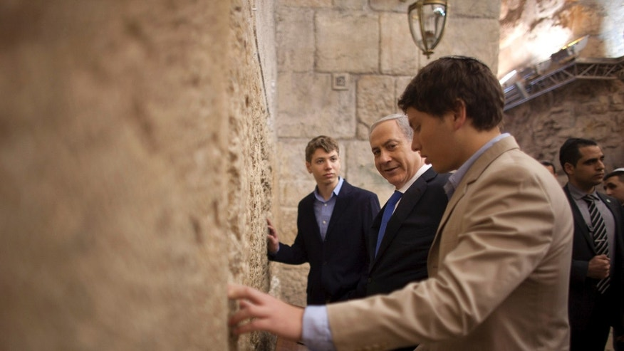 Jan. 22, 2013 - FILE photo of Israeli Prime Minister Benjamin Netanyahu, center, praying with his sons Yair, background, and Avner, right,  at the Western Wall, the holiest site where Jews can pray, in Jerusalem. News that 23-year-old Yair Netanyahu is dating a non-Jewish Norwegian university student has generated interest not just in gossip columns but also among religious lawmakers who warn of assimilation.