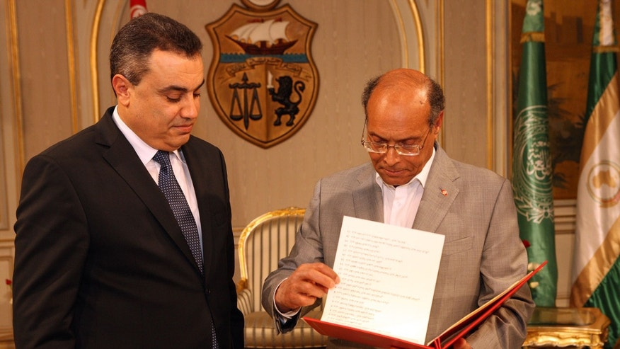 Interim Prime Minister, Mehdi Jomaa, left, presents the list of the members of his government to Tunisian President Moncef Marzouki during the new government presentation ceremony at the presidential palace in Carthage near Tunis, Sunday, Jan. 26, 2014. Tunisia's interim prime minister announced on Sunday his new government following a 24-hour delay over the post of interior minister. Mehdi Jomaa, the interim prime minister, had been working since Jan. 10 to form a government of technocrats to guide the country to new elections after a political crisis that began last year between Islamists and the opposition following the assassination of an opposition politician. (AP Photo/Hassene Dridi)