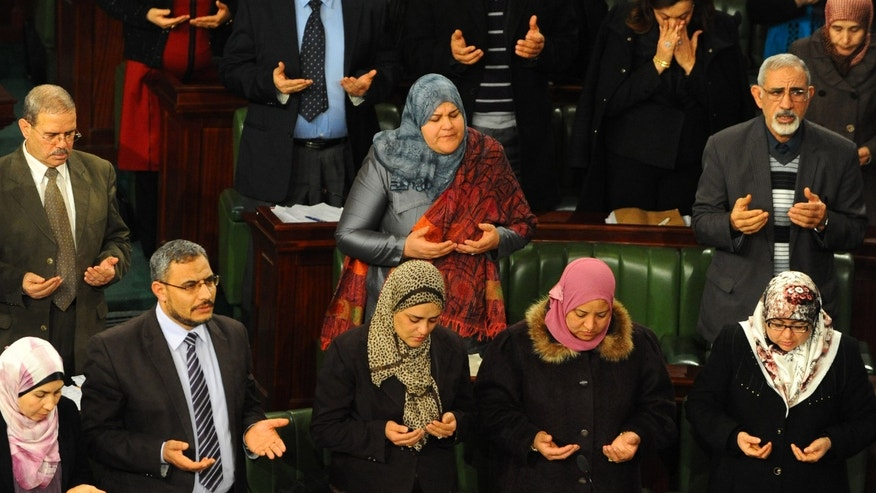 In this photo dated Thursday, Jan. 23, 2014, members of the Constitutional Assembly pray during a minute of silence for the passing of a late deputy, Mohamed Allouche, before a session as part of the debates on the new constitution in Tunis, Tunisia. The spokesman for Tunisia's Constitutional Assembly says a final vote on a new constitution will take place Saturday, now that members have approved each of the new articles in the historic document. (AP Photo/Hassene Dridi)