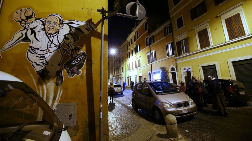 "A graffiti depicting Pope Francis as Superman and holding a bag with a writing which reads: ""Values"" is seen on a wall of the Borgo Pio district near St. Peter's Square in Rome, Tuesday, Jan. 28, 2014. It wasn't enough that Pope Francis was named Time magazine's ""Person of the Year"" or that he fronted this week's Rolling Stone magazine. Now there's SuperPope graffiti sprouting up around the Vatican. The white caped crusader appeared Tuesday on a wall just off Borgo Pio, a tiny cobble-stoned street near St. Peter's Square. In typical superhero fashion, Francis' right fist is thrust in the air, leading him in flight, while his left clutches his black satchel. ""Valores,"" or values in Spanish, is written across it. The artist is identified only as Maupal. Francis has charmed the masses with his simplicity and message of helping the poor, even as he has cracked down on Vatican waste and corruption. The Vatican communications office approved of the image, tweeting a photo Tuesday. (AP Photo/Gregorio Borgia)"