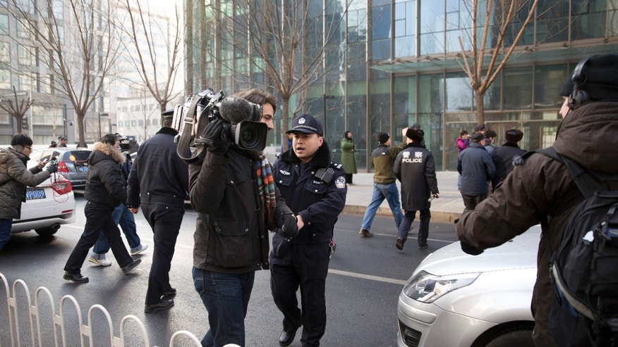 In this Sunday, Jan. 26, 2014 photo, policemen try to block journalists from interviewing Xu Zhiyong's lawyer Zhang Qingfang as he speaks to the media near the No. 1 Intermediate People's Court, in Beijing. The government is intensifying efforts to control foreign media coverage of China, blocking websites, harassing reporters trying to cover trials of activists in Beijing and thwarting efforts by The New York Times to station new journalists on the mainland. (AP Photo/Andy Wong)