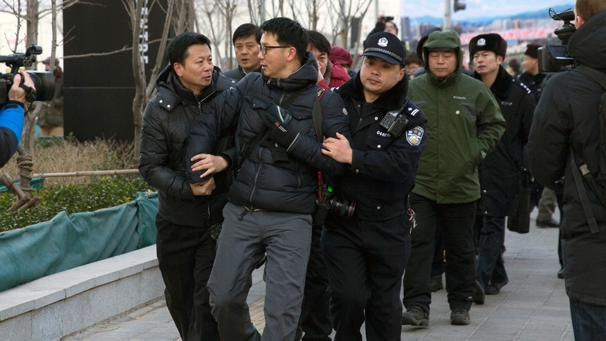 In this Sunday, Jan. 26, 2014 photo, Chinese policemen manhandle a foreign photographer, center, as he photographs Zhang Qingfang, lawyer of legal scholar and founder of the New Citizens movement Xu Zhiyong, speaking to the media near the No. 1 Intermediate People's Court, where Xu appeared for his verdict in Beijing. The government is intensifying efforts to control foreign media coverage of China, blocking websites, harassing reporters trying to cover trials of activists in Beijing and thwarting efforts by The New York Times to station new journalists on the mainland. (AP Photo/Andy Wong)