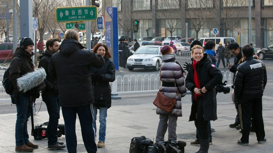 In this Sunday, Jan. 26, 2014 photo, foreign journalists are watched by police as they gather near a street corner after being barred from getting near the No. 1 Intermediate People's Court, where legal scholar and founder of the New Citizens movement Xu Zhiyong appeared for his verdict in Beijing. The government is intensifying efforts to control foreign media coverage of China, blocking websites, harassing reporters trying to cover trials of activists in Beijing and thwarting efforts by The New York Times to station new journalists on the mainland. (AP Photo/Andy Wong)