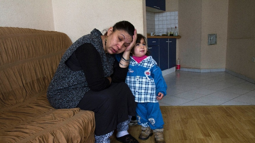 Dzemile Dibrani, the mother of Leonarda Dibrani, sits alongside her baby daughter Medina after a ruling by a French court on their appeal for French residency at a shelter house in the town of Mitrovica, Tuesday, Jan. 28, 2014. A French court barred Tuesday the return to France of a Roma family including the teenage girl whose expulsion to Kosovo became a cause celebre. Leonarda Dibrani was detained in October as she got off a bus from a school trip, sparking rowdy protests in Paris and other cities. (AP Photo/Visar Kryeziu)