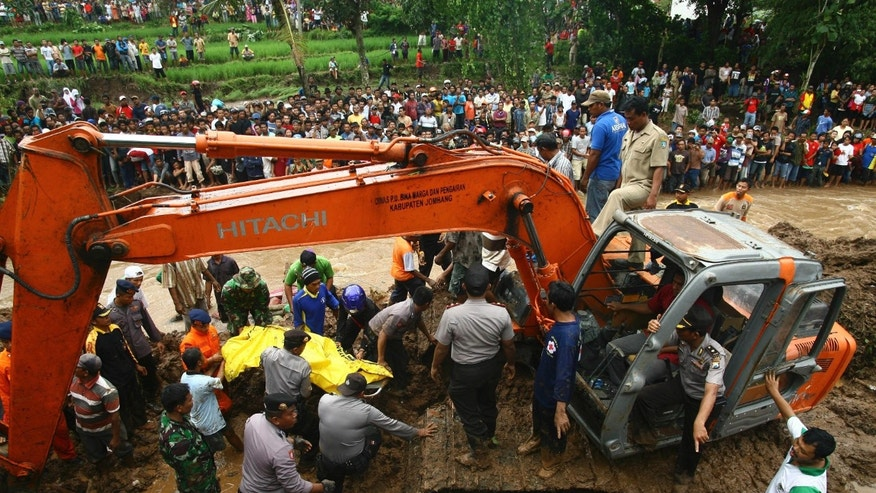Rescuers recover the body of a landslide victim in Jombang, East Java, Indonesia, Tuesday, Jan. 28, 2014. Two landslides triggered by torrential rain killed more than a dozen of people and left some others missing on Indonesia's main island of Java, a government official said Tuesday. (AP Photo/Trisnadi)