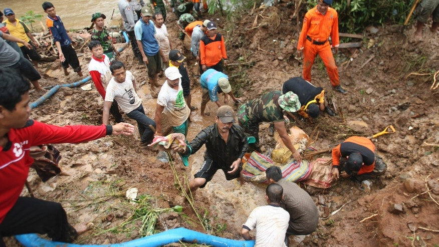 Rescuers search for the victims of a landslide in Jombang, East Java, Indonesia, Tuesday, Jan. 28, 2014. Two landslides triggered by torrential rain killed more than a dozen of people and left some others missing on Indonesia's main island of Java, a government official said Tuesday. (AP Photo/Trisnadi)