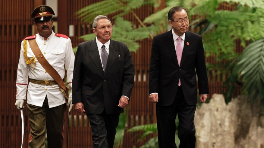 Cuba's President Raul Castro, left center, and U.N. Secretary General Ban Ki-moon, right, review an honor guard at the Revolutionary Palace in Havana, Cuba, Monday, Jan. 27, 2014. (AP Photo/Pool)