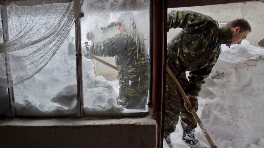 Romanian soldiers clear snow from around an old house in the village of Vadu Pasii, Romania, Tuesday, Jan. 28, 2014. Snow storms are forecast for the coming days in the already affected southeastern regions of Romania in which road and rail traffic were badly disrupted and the army was called in to assist in the worst hit areas. (AP Photo/Vadim Ghirda)