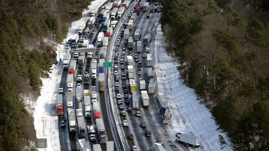 In this aerial photo, traffic is snarled along the I-285 perimeter north of the metro area after a winter snow storm, Wednesday, Jan. 29, 2014, in Atlanta.  Georgia Gov. Nathan Deal said early Wednesday that the National Guard was sending military Humvees onto Atlanta's snarled freeway system in an attempt to move stranded school buses and get food and water to people. Georgia State Patrol troopers headed to schools where children were hunkered down early Wednesday after spending the night there, and transportation crews continued to treat roads and bring gas to motorists, Deal said. (AP Photo/David Tulis)